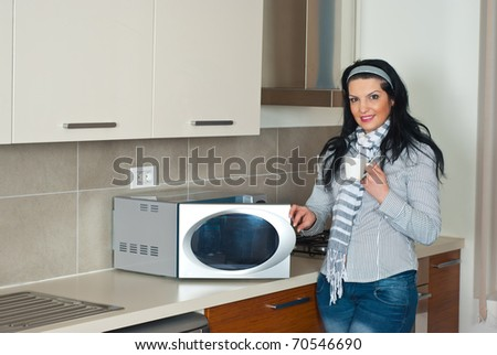 Attractive woman drinking coffee and opening microwave oven in her kitchen - stock photo