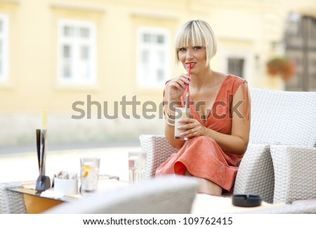 attractive woman drinking iced coffee in outdoor cafe chair - stock photo