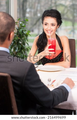 attractive woman drinking juice with straw. back view of man listening to girl at lunch break - stock photo