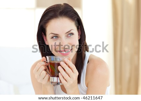 Attractive woman drinking tea sitting on her bed - stock photo