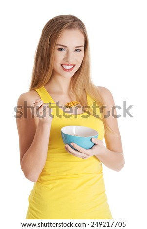 Attractive woman eating cereals from a bowl. Isolated on white. - stock photo