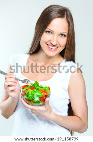 attractive woman eating salad with vegetables. healthy food. - stock photo