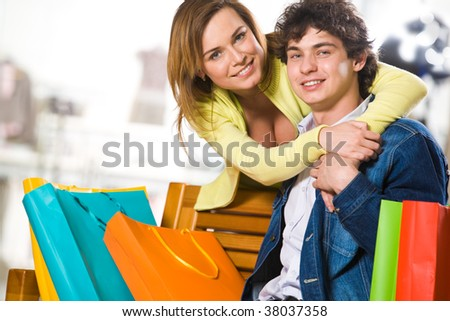 Attractive woman embracing her boyfriend in the mall - stock photo