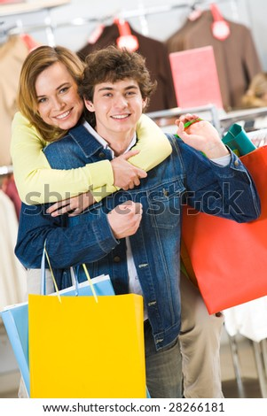 Attractive woman embracing her boyfriend while both looking at camera with smiles - stock photo