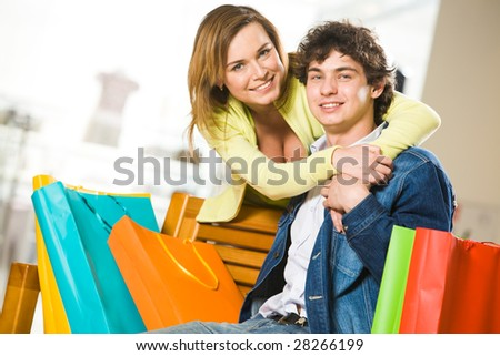 Attractive woman embracing her boyfriend while he sitting on bench in mall - stock photo