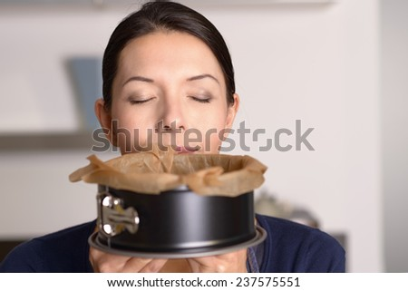 Attractive woman enjoying aroma of a freshly baked cake in a baking tin which she has just removed from the oven, concealing her lower face with closed eyes above - stock photo