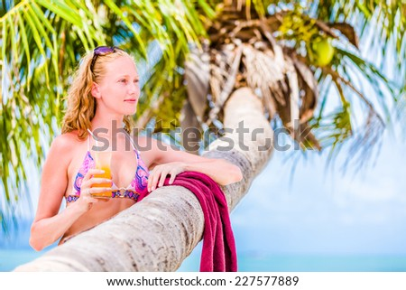 Attractive woman enjoying at the sun, sunbathing and drink cocktail - stock photo