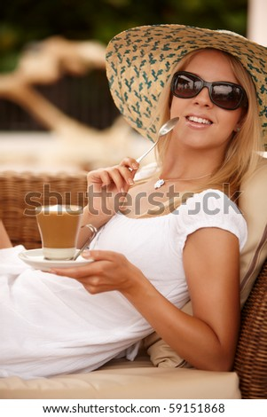 Attractive woman enjoying coffee on a vacation during summer day