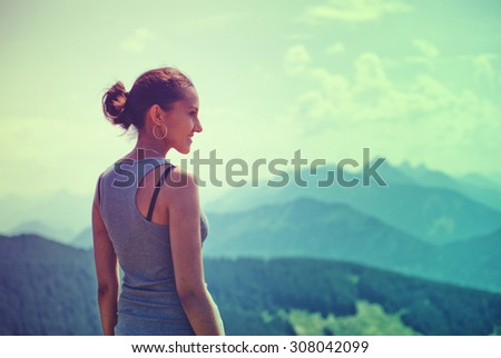 Attractive woman enjoying the beauty of nature standing on a mountain summit looking out over the alps and distant mountain peaks with the glow of the evening sun lighting up her face - stock photo