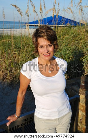 Attractive Woman enjoying the early morning sun at the beach - stock photo