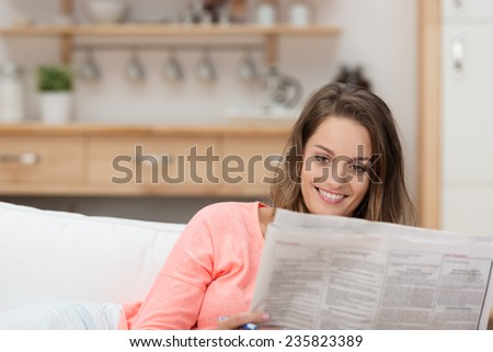 Attractive woman enjoying the morning newspaper smiling to herself as she catches up on the news while relaxing on the sofa - stock photo