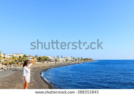 Attractive woman  enjoying the view of Aegean sea at Santorini, raising hand up in the early morning by the volcanic beach on Santorini, Mediterranean sea, Greece - stock photo