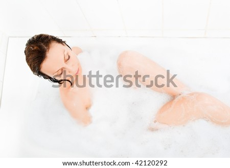Attractive woman enjoys  in the bathtub.