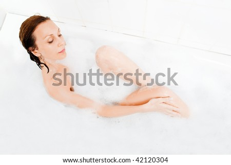 Attractive woman enjoys  in the bathtub. - stock photo