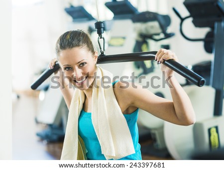 Attractive woman exercising at gym, biceps workout on a machine. - stock photo