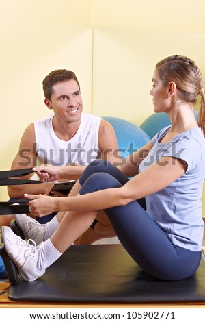 Attractive woman exercising in fitness center and talking to male fitness trainer - stock photo