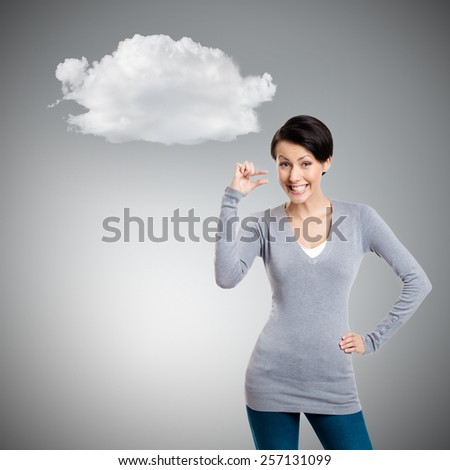 Attractive woman gestures small amount, isolated on grey background with cloud - stock photo