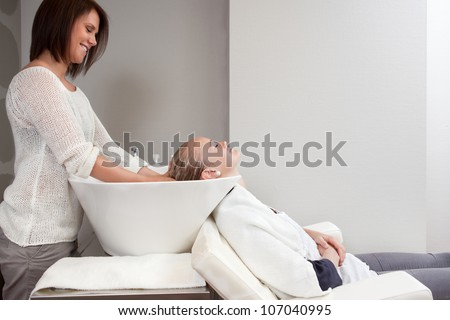 Attractive woman getting her hair washed at a beauty salon.