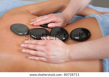 attractive woman getting spa hot stone treatment - stock photo