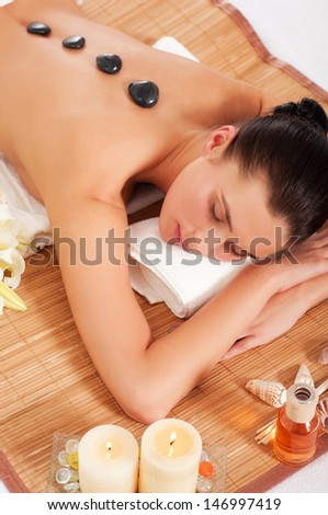 Attractive woman getting spa treatment isolated on white background. Hot Stones Massage  - stock photo