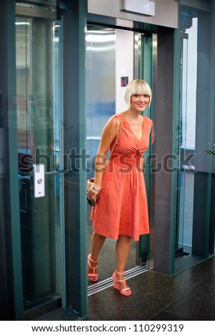 attractive woman going out of the elevator - stock photo