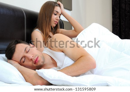 Attractive woman grieves while her husband is sleeping at home - stock photo