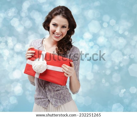 Attractive woman hands a present wrapped in red paper with white bow on blue light background - stock photo