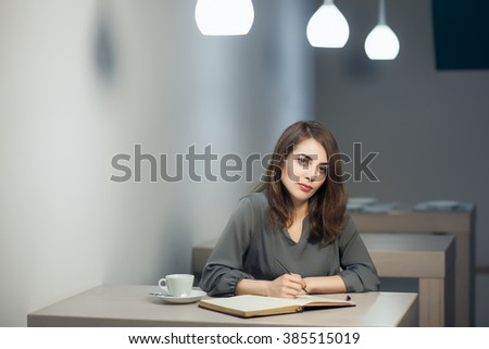 attractive woman has a cup of tea in restaurant and making notes in pad; writer makes a novel; poet writes a poem; - stock photo