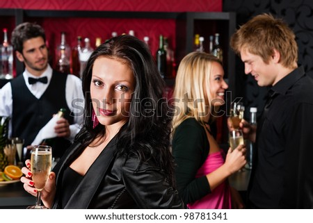 Attractive woman having drink with friends at cocktail bar - stock photo
