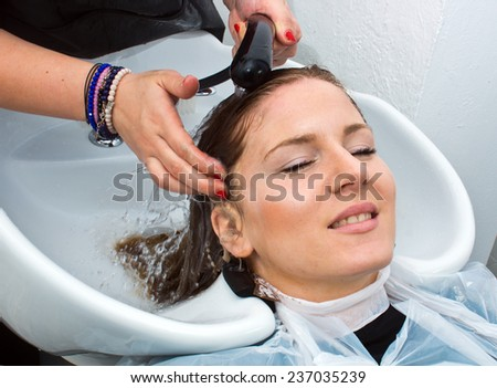 attractive woman having hair washed in salon