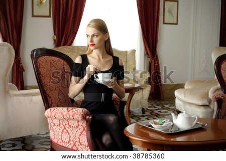 attractive woman having tea time in a luxury hotel room - stock photo
