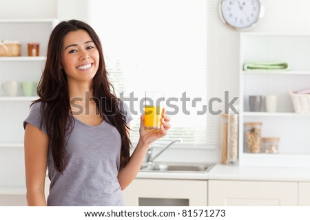 Attractive woman holding a glass of orange juice while standing in the kitchen - stock photo