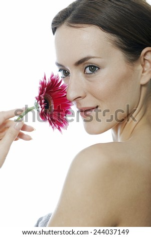 Attractive woman holding a red flower near her face - stock photo