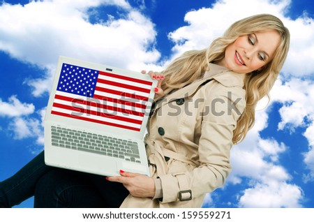 attractive woman holding laptop with usa flag on sky background - stock photo