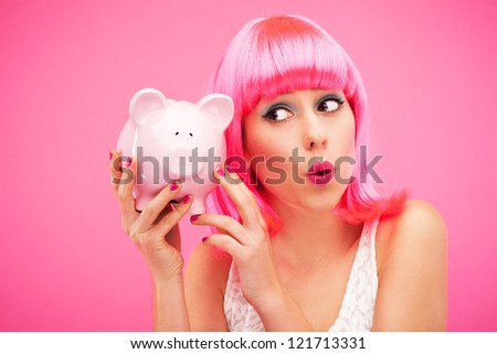 Attractive woman holding piggy bank - stock photo
