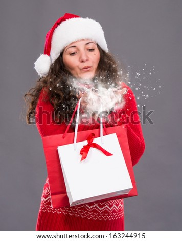 Attractive woman holding shopping bags blowing snow, christmas, x-mas, winter,