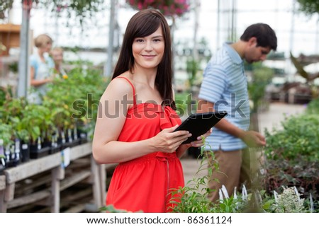 Attractive woman holding tablet pc with people in background