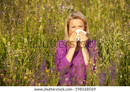 Attractive woman in a flower field with allergic symptoms
