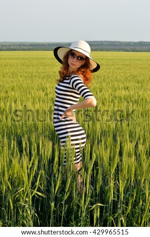 Attractive woman in a hat and sunglasses, summer photo in the field. Girl in the sea dress. Sport Lady. - stock photo