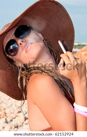 attractive woman in a hat smoking a cigarette - stock photo