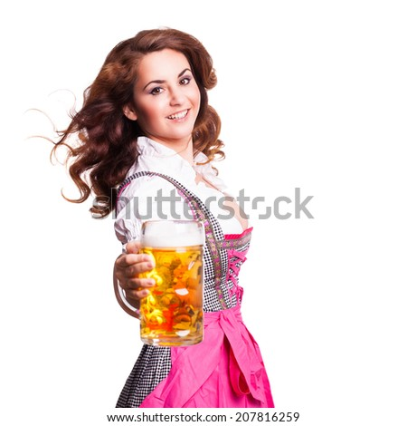 attractive woman in a pink dirndl holding a beer - stock photo