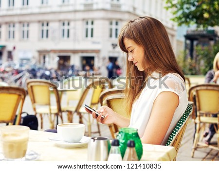 Attractive woman in a street cafe reading a text message from her phone - stock photo