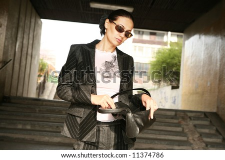 Attractive woman in a suit posing on the stairway - stock photo
