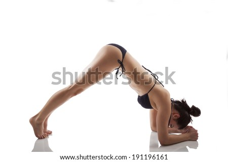 Attractive woman in bikini doing yoga stretching isolated over white background. Fitness, flexibility and freedom.