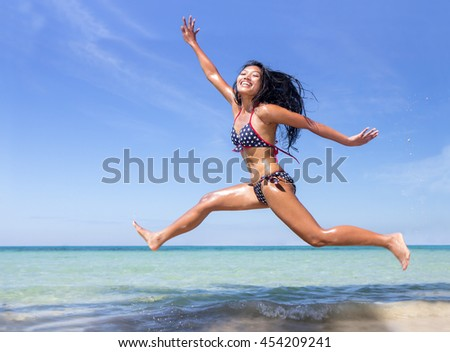 Attractive woman in bikini jumping on the sea beach. Enjoy of a tropical vacation. Cheerful woman in swimsuit running along the coast.