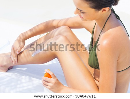 Attractive Woman In Bikini Sitting At Beach With Sun Protection Cream - stock photo