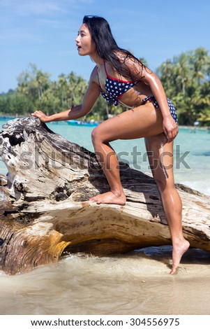 attractive woman in bikini standing on the withered trunk over the sea - stock photo
