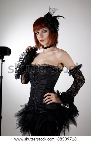 Attractive woman in black corset, gloves and tutu skirt, studio shot - stock photo