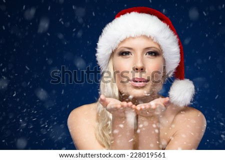 Attractive woman in Christmas cap blows kiss, winter background - stock photo