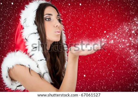 attractive woman in Christmas costume blowing snow form hand - stock photo